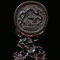 A <b>silver</b> plated bronze mirror with carved wood base, China, Ming Dynasty, 16th century
