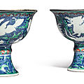 An extremely rare pair of blue-ground iron-red and green-enameled 'Mythical beasts' <b>stem</b> <b>cups</b> , Wanli marks and period (1573-161