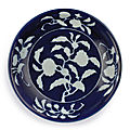 An exceptionally rare <b>and</b> important <b>blue</b> <b>and</b> <b>white</b> <b>reverse</b>-<b>decorated</b> 'pomegranate' dish, Mark <b>and</b> period of Xuande (1426-1435)
