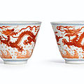 A fine pair of iron-red <b>dragon</b> <b>cups</b>, Seal marks and period of Qianlong