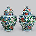 A pair of wucai '<b>Boy</b> <b>and</b> <b>Peony</b>' <b>jars</b> <b>and</b> covers, 17th century