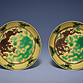 A pair of fine yellow-ground <b>aubergine</b> <b>and</b> <b>green</b>-enamelled 'Dragon' dishes, Kangxi six-character marks <b>and</b> of the period
