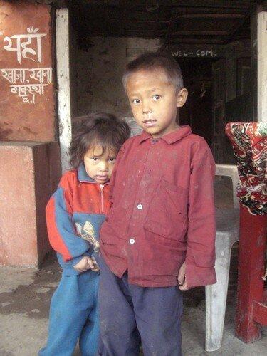 Enfants, un peu impressionnes par l'appareil photo et les etrangers