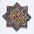 A Kashan lustre painted star-shaped tile with a rosace, <b>early</b> <b>14th</b> <b>century</b>