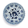 An exceptional and rare blue and <b>white</b> barbed 'grape' charger, Ming Dynasty, Yongle Period (1402-1424)