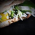 Pain plat cuit au feu de bois, boutons de fleur d'ail des ours, fromage de chèvre et œuf au plat