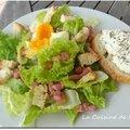 Salade au chèvre chaud, lardons, croutons, oeuf mollet, vinaigrette à la framboise et moutarde