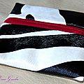 Du skaï façon <b>peau</b> de <b>zèbre</b> ... un zip bordeaux ... une doublure rouge étoilée ... un porte-monnaie unisexe ?