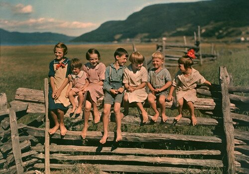 Seven siblings sit on a wooden fence in Quebec Canada May 1939Photograph by Howell Walker National Geographic