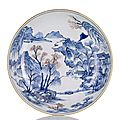A fine and rare underglaze blue and copper red decorated deep porcelain plate in <b>the</b> style of <b>the</b> 'Master of <b>the</b> <b>Rocks</b>'.