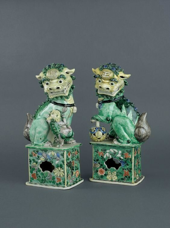 Pair of famille verte biscuit porcelain large models of seated Buddhist lions on openwork rectangular stands, Early Kangxi