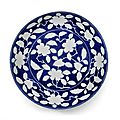 A reserved-decorated blue-ground 'floral' dish, Yongzheng six-character mark and of the period