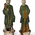A pair of <b>green</b> <b>and</b> <b>amber</b>-<b>glazed</b> <b>pottery</b> figures of attendants, Ming dynasty (1368-1644)