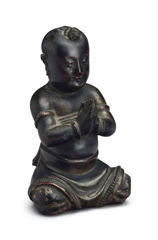 A small lacquered wood figure of a seated boy, China, Ming dynasty (1368-1644)