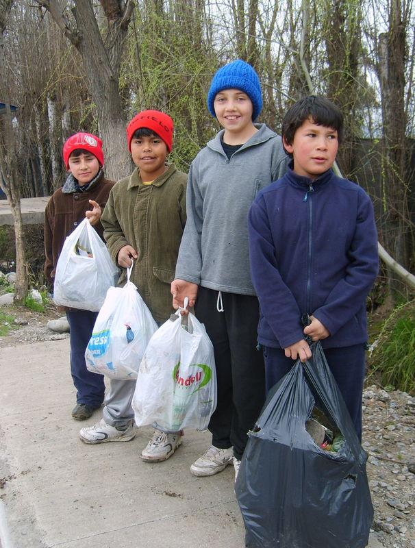 4 niños del equipo limpiando el canal del Camino Real de Graneros