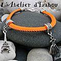 Simple tour mais agrémenté de deux <b>breloques</b> : tour eiffel et robe, ce bracelet est en cuir orange fluo et marron !