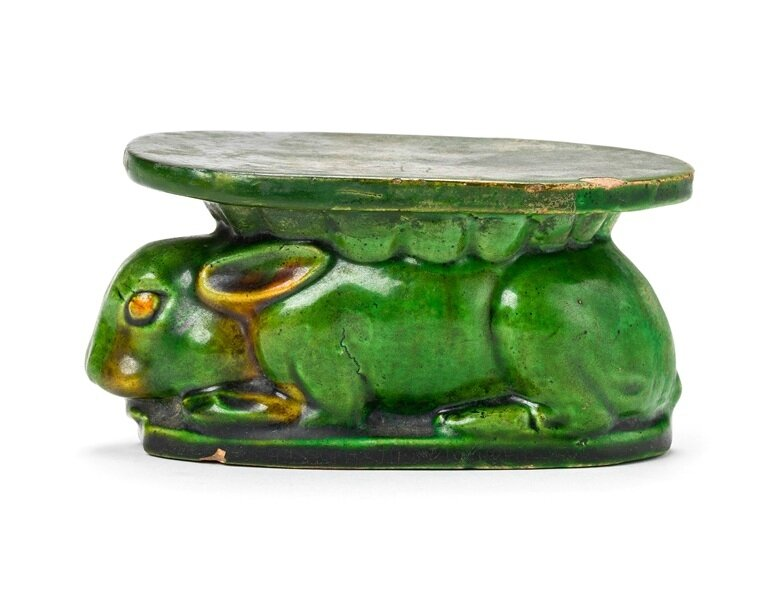 A green and amber-glazed rabbit-form pillow