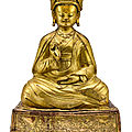 A large gilt-copper <b>repoussé</b> figure of Padmasambhava. Tibet, 17th century