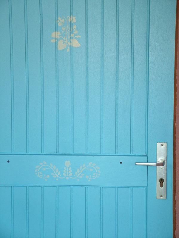 Porte peinte en bleu avec des pochoirs fleurs.