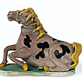 A rare aubergine, yellow, black and <b>green</b>-<b>glazed</b> biscuit figure of a recumbent horse, Qing dynasty, Kangxi period (1662-1722)