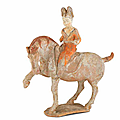 A painted pottery figure of a female polo player, Tang Dynasty