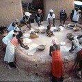 Les femmes font de le farine à la meule publique