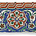 An Iznik polychrome pottery border tile with composite flowerhead and key fret red border, Turkey, <b>circa</b> <b>1550</b>-<b>1600</b>