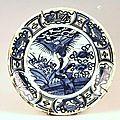 Delft. plat creux en faïence bleu-blanc à décor d'un oiseaux dans un paysage au centre et sinisant sur l'aile. xixème siècle