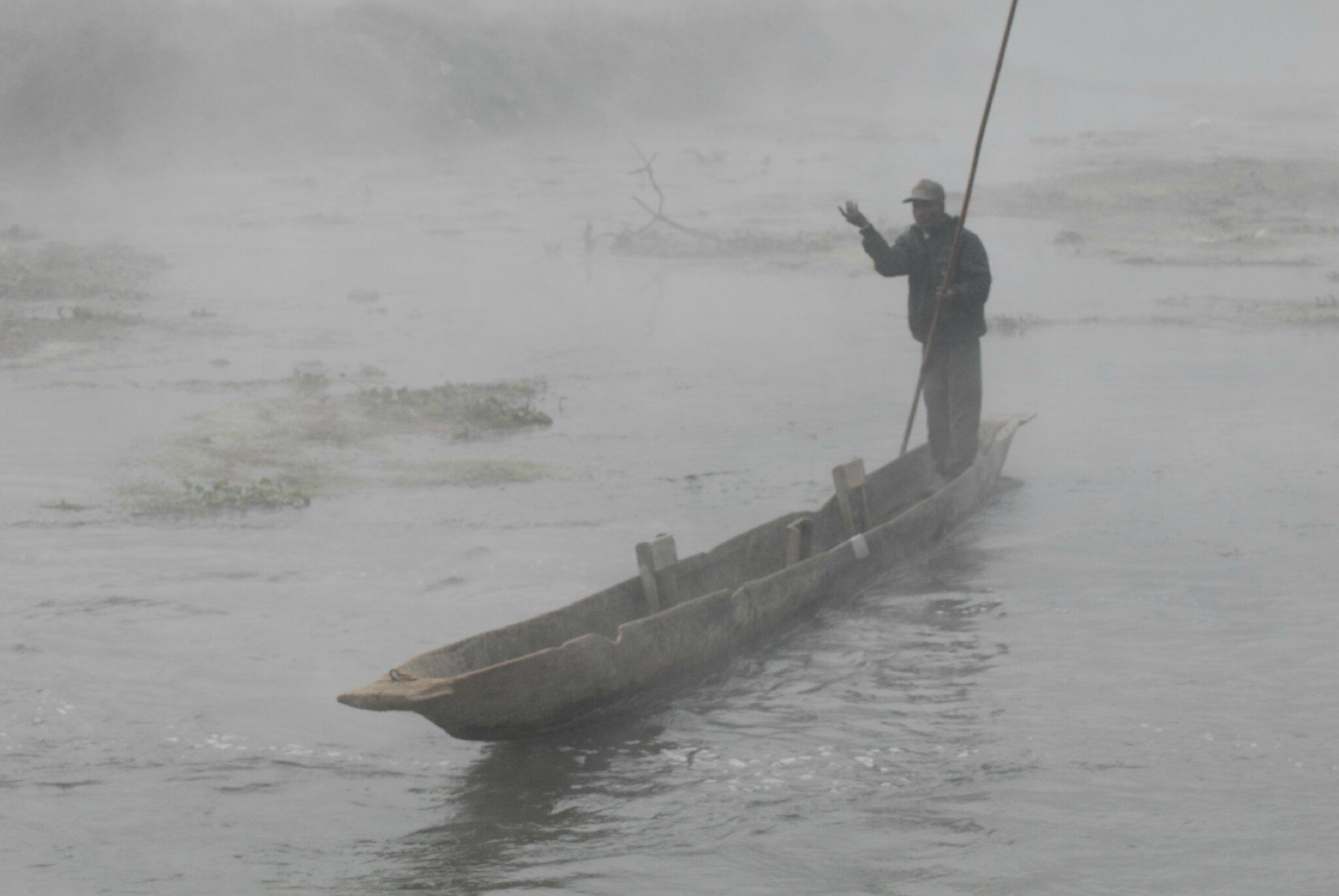 pêcheur à pirogue au petit matin