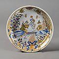 Moulins. assiette à décor polychrome au centre de deux chinois attablés, xviiie siècle
