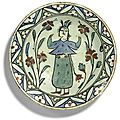An iznik polychrome pottery dish with standing figure, turkey, 17th centur