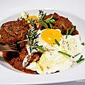 Boulettes en sauce tomate/poivron/ olives, herbes <b>aromatiques</b> avec des oeufs au plat
