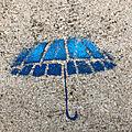Un parapluie bleu au pied de la <b>tour</b>