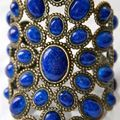 Andrew <b>Gn</b>, jewelled statement cuff cast in bronze with lapis blue glass cabochons in beaded oval settings