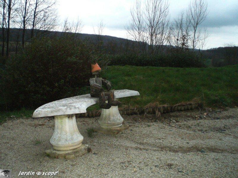 Bonhomme de bois assis sur un banc de pierre