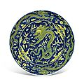 A <b>blue</b>-<b>ground</b> <b>yellow</b>-<b>enamelled</b> 'Dragon' dish, Qianlong six-character seal mark in underglaze <b>blue</b> and of the period (1736-1795)
