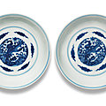 A pair of blue and white 'dragon and pheonix' <b>saucer</b>-<b>dishes</b>, Kangxi six-character marks and of the period (1662-1722)