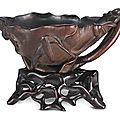 A carved rhinoceros horn 'Millet and Flowers' libation cup, Qing dynasty, 18th century